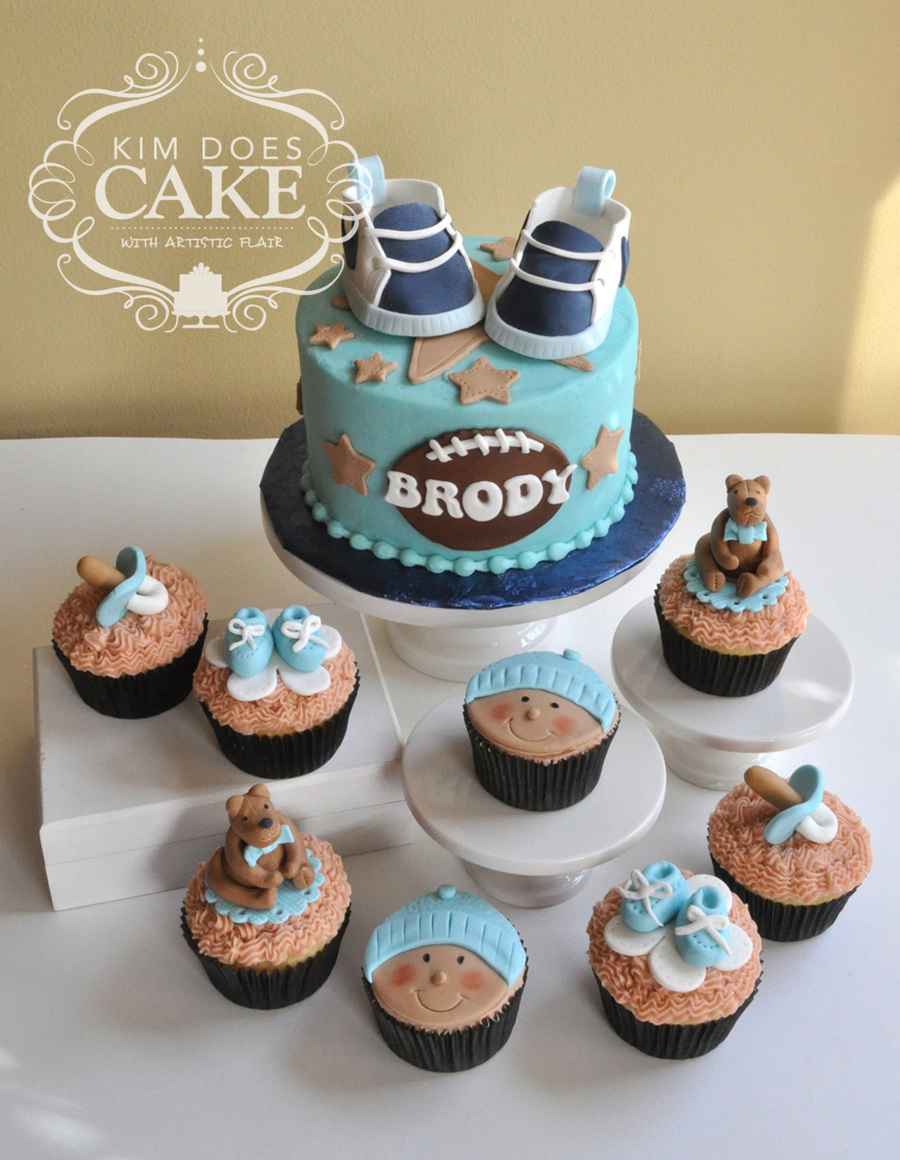 A Sports Themed Baby Shower Cake With Nike Gum Paste Shoes On Top. Cupcakes  Have Bears, Baby Faces, Pacifier And Bootie Toppers On Them.