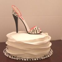 Stiletto Shoe And Ruffled Fondant stiletto shoe made from fondant and gumpaste on top of 10 in round cake detailed with ruffled fondant