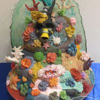 Scuba Diving Coral Reef Cake With Working Dive Light And Edible Glass Water  Vanilla Buttercream cake covered in fondant live rock to make the coral reef base. Topped with gum paste scuba diver holding fondant...