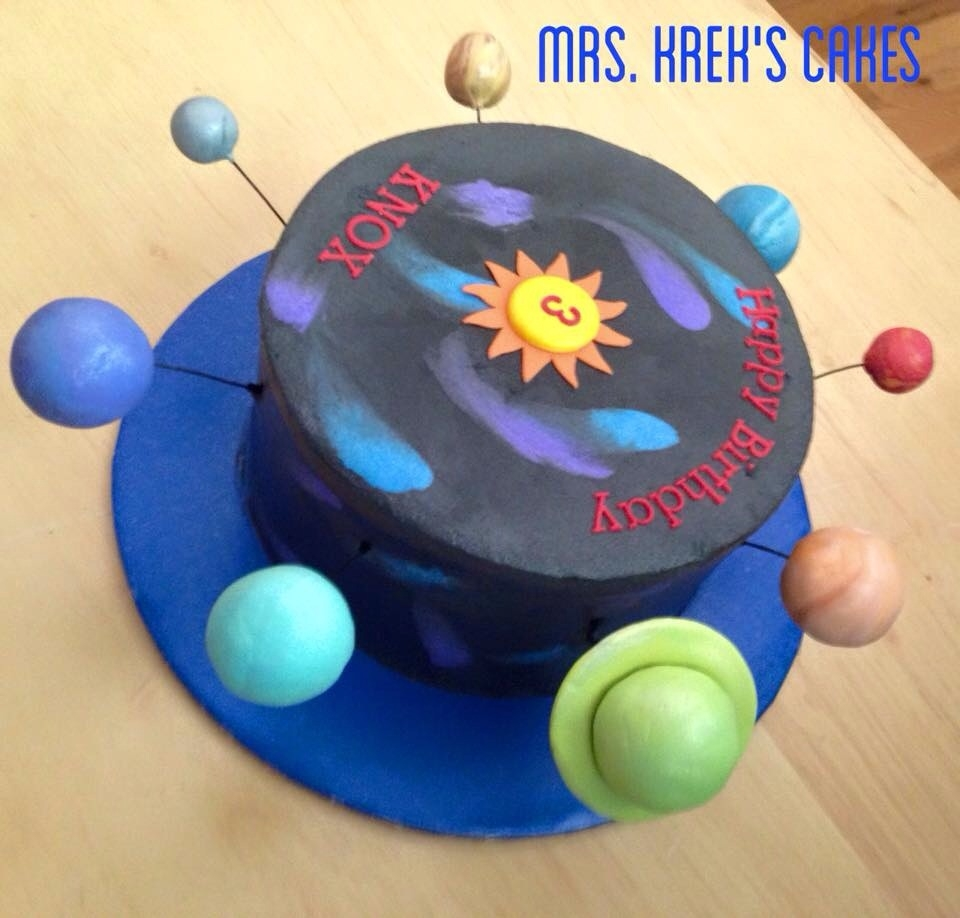 Solar System Cake Iced in buttercream. Planets are styrofoam covered in fondant.