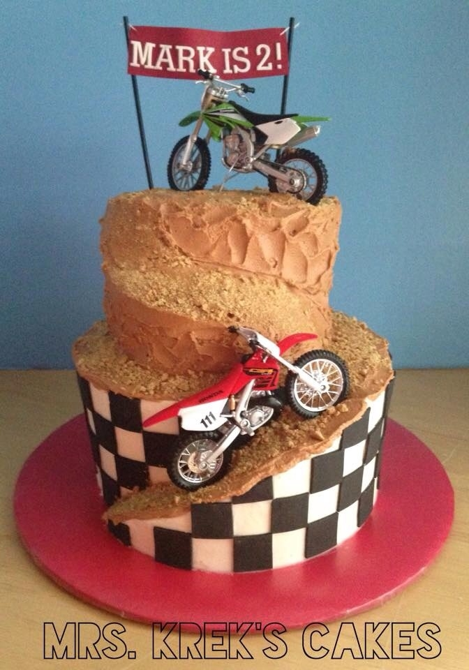Dirt Bike Cake Iced in buttercream. Dirt is graham crackers. Black fondant squares. Bikes are toys. Pennant is coffee stirrers, sugar sheet banner,...