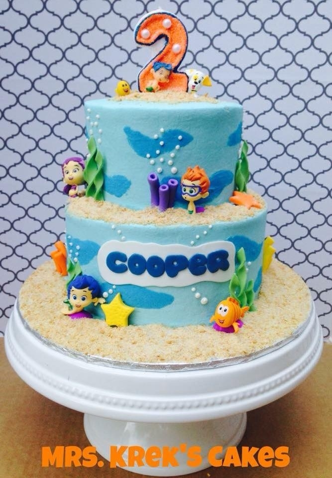 Bubble Guppies Cake Iced in buttercream, fondant decorations. Characters are toys. Candle made by artist on Etsy. Sand is grahams, sugar and sanding sugar.