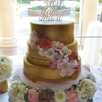 Gold And Pink Wedding Cake Three tiered wedding cake with gold covered fondant, sugar lace and pink flowers.