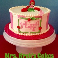 Strawberry Shortcake Cake Iced in buttercream with fondant decorations. Character is a toy.