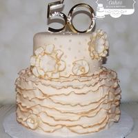 "50Th Anniversary 6"" & 8"" cakes iced in fondant w/fondant decorations. Everything gold was hand painted. The 50 topper was provided by the..."