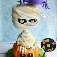 Halloween Cake Harmless Happy little spider Hanging on His Horrific, Haunting, Handsome friend the mummy peeking out of a spooky pumpkin. 3d structured...