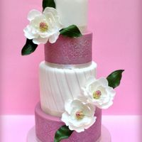 Sugar Magnolias Wedding Cake 4tiered wedding cake with sugar magnolias. Decorations also include various techniques such as embossment, lustre effect and pleats.