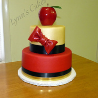 Snow White Apple Cake Butter cake iced in buttercream icing with fondant bow and apple.
