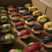 Hot Wheel Theme Vanilla cupcakes with buttercream and cars made out of melted chocolate and hand painted wheels.