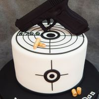 "Gun And Target Gun is styro foam covered in fondant, 7"" vanilla cake with raspberry"