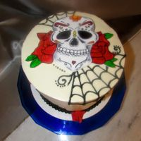 Day Of The Dead Cake is covered with Italian Meringue Buttercream. Skull is gumpaste painted with food color.