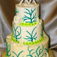 Coral On The Beach Chocolate wedding cake with IMBC. Teal coral all piped on, shells made of melting chocolate. The topper was created using starfish the...