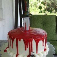 Bloody Cake 8 inch cake with butter cream frosting.. blood is red ganache and the knife is plastic.