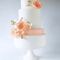 Modern White Wedding Cake Clean and simple four tier modern white wedding cake with peach English roses and gold-plated leaves by Olga Zaytseva