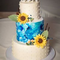 Blue And Sunflowers Fall wedding cake featuring gum paste sunflowers and berries. The center tier is water colored wafer paper