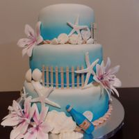 Beach Wedding Cake Covered in fondant with gumpaste flowers & chocolate seashells.