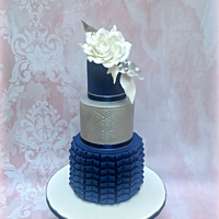 Navy Blue And Silver Cake Elegant three tier cake in navy blue and silver lustre finish topped with a full open gumpaste rose and foliage in shades of white and...