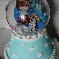 Frozen Snow Globe Strawberry cake in buttercream. The globe is glass, decorated with fondant snowflakes. The inside scene is a cut out of foam, paper plate...