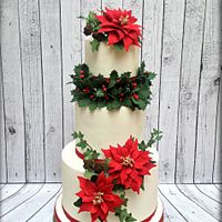 Poinsettia Christmas Cake Three tiered cake inspired by Christmas nature elements such as poinsettias, holly leaves, ivy leaves and pine cones, all made out of...