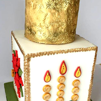 Quilled Christmas Cake A 2 tier cake with gold embossing on the top tier and chocolate pinecone cake topper with hypericum berries. The second tier is also in...