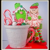 Standing Elf Place Card And 3-D Cookie Mug Edible 3-d cookie mug filled with chocolate mint candies, and a standing elf place card cookie with candy necklace beads on a skewer for...