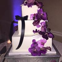Purple Orchids Wedding Cake Three tiered square wedding cake adorned with shades of fresh purple orchids. Black ribbon on side of cake to match the bride's dress...