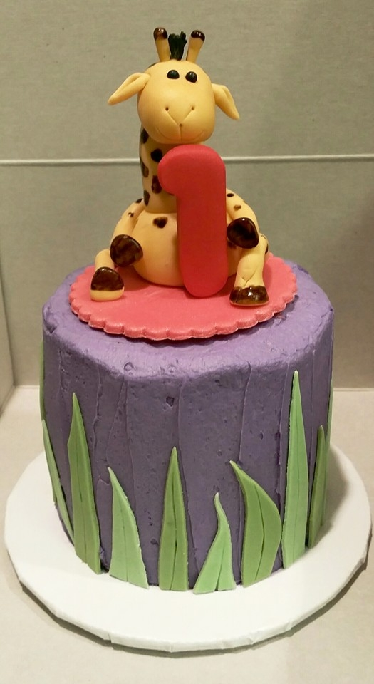 Giraffe Smash Cake Buttercream iced cake with jungle grass all around. Giraffe holding #1.