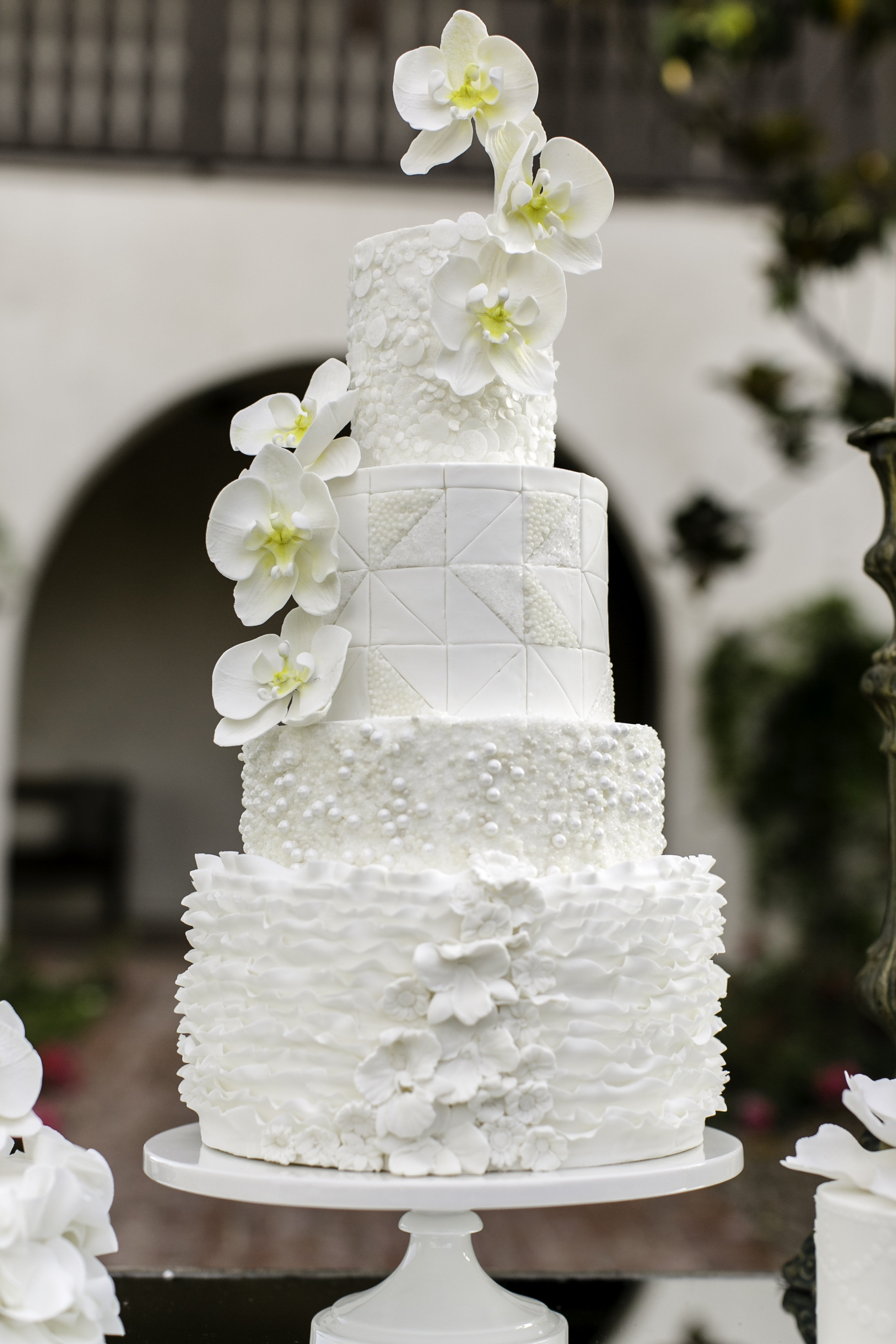 Orchid Wedding Cake   Moth Orchids made of gumpaste adorn this white textured wedding cake with fondant frills, pearls, and geometric patterns