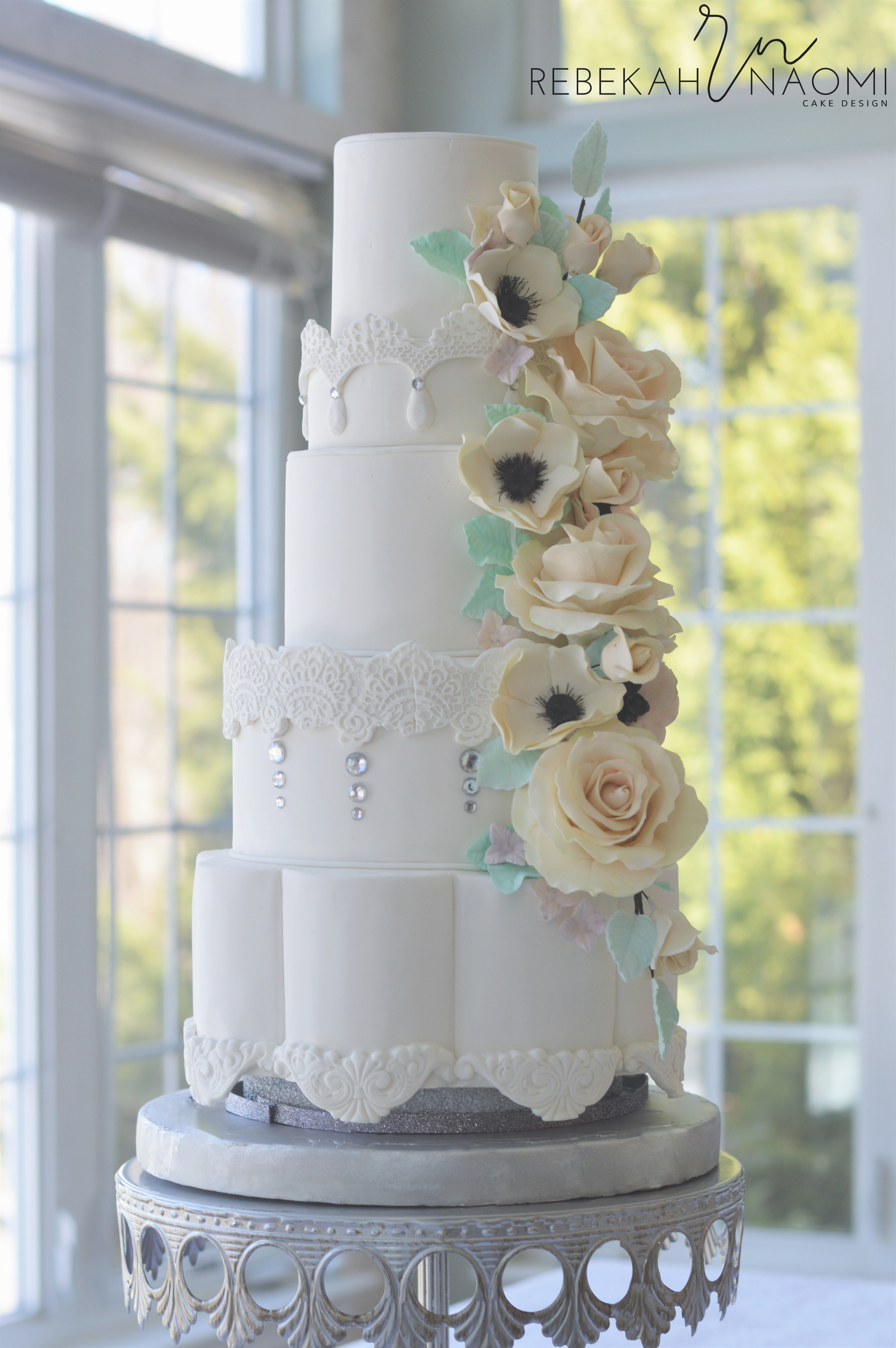 Winter Wedding Cake An all white wedding cake with a petal bottom tier and lace appliques. The cake features a floral cascade of roses and anemones in soft...