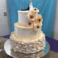 3 Tier Round Wedding Cake 3 tier round wedding cake with buttercream frosting and fondant ruffles on bottom of cake. Gum paste flowers.