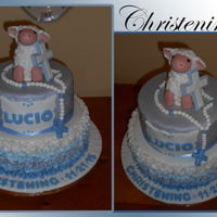 Baptism 2 tiered baptism cake, all covered in fondant. Top tier with diamond pattern, bottom tier covered in ombre ruffle effect. Lamb and cross...