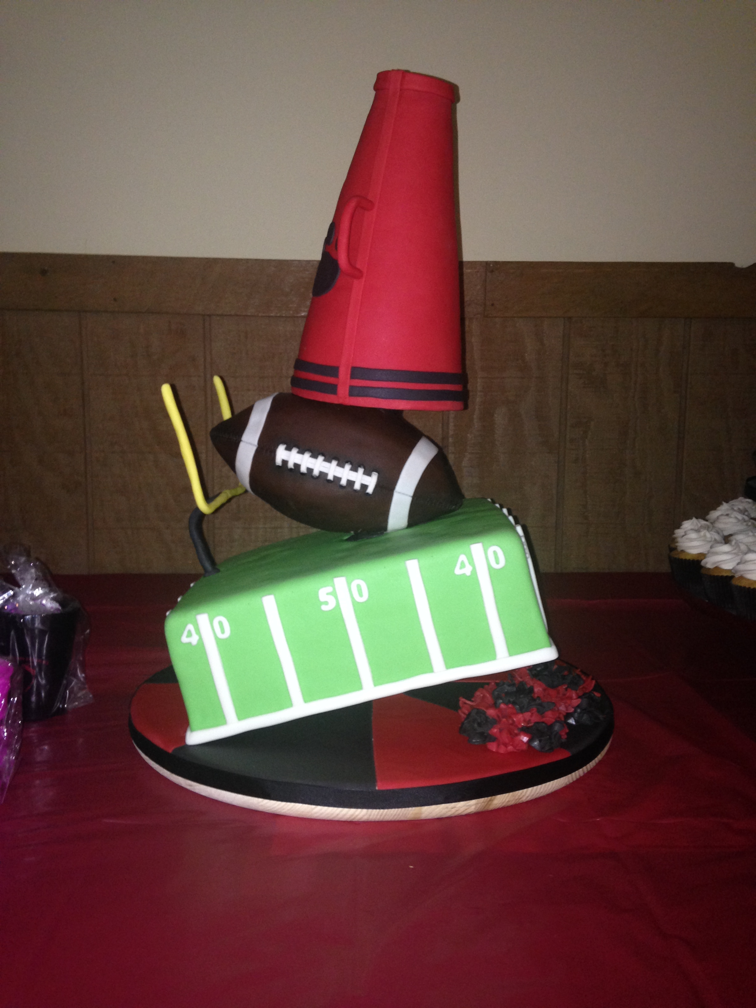 Football Cheer Topsy Turvy Cake  Football field themed bottom tier covered in mmf, 3D football center tier covered in modeling chocolate, megaphone top tier covered in mmf...
