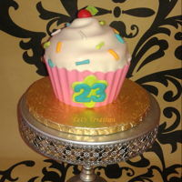 Giant Cupcake pink chocolate liner, chocolate cake with mocha frosting, fondant covered top and sprinkles