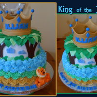 King Of The Jungle 2 tiered first birthday cake, top tier covered in fondant, bottom tier covered in buttercream rosette. Gold crown and lion made of fondant...