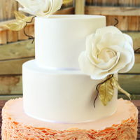 Peach-Colored Ruffled Wedding Cake Peach color ruffle design on the bottom tier. Shimmer finish on two top tiers. Gum paste peony rose with golden leaves. I used sugar flower...