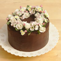 Spring Floral Wreath Cake Chocolate and rose cake, covered with dark chocolate ganache, topped with a wreath of sugar roses, apple blossom, daisies and buds.