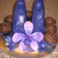 A Pair Of Shoes For You! A pair of candy melt high heel shoes with molded bows. Ganache frost on chocolate cupcakes. The arrangement was decorated with a gum-paste...