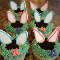 Bunny Cupcake Easter cupcakes: royal icing ears, cookie crumbs for dirt and buttercream piped grass and flower. Kids and adults were impressed!