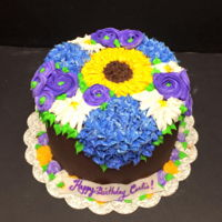 Buttercream Bouquet Cake Cake covered in ganache and buttercream flowers including ranunculus, daisies, hydrangea and sunflowers