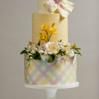 Festive Easter Cake This cheerful cake was inspired by the fragrant flowers and colorful ribbons of Easter. The sugar flowers include daffodils, open rose,...