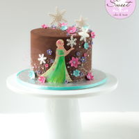 Frozen Fever Ganache Cake  A chocolate ganache-covered 6 inch, Frozen Fever themed cake decorated with sparkly glitter dust, sugar pearls, flower blossoms, sugar...