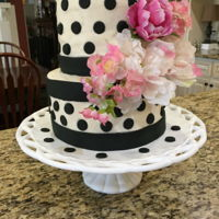 Kate Spade Like Cake White buttercream with black fondant dots with added silk flowers