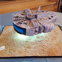 Millennium Falcon Hovering Star Wars 3D Millennium Falcon grooms cake. Fondant with fondant detail. Airbrushed and dusted.