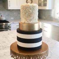 Ruffled Rosette/ Gold/ Black And White Striped Cake This is a 3 tiered chocolate mud cake with whipped buttercream frosting filling and chocolate ganache shell. Stripes were made with...