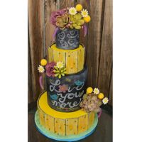 Rustic Chalkboard Cake Yellow painted aged wood paneled cake with chalkboard tiers. Hand made succulents, daisies, billy balls and lavender.