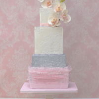 Soft Pink Ruffles Wedding Cake With Orchids Four tiers square wedding cake with soft pink ruffles, ivory lustre and orchids.The different patterns on each tiers and the silver...