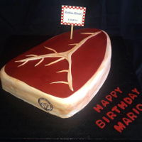 Steak Cake Strawberry cake carved out and covered in ivory fondant, topped with maroon fondant