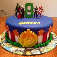 "Avenger Birthday Cake A 10"" buttercream covered cake with The Avenger's theme. Handcut letters and Avengers icon on a clear glass cake plate covered..."