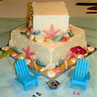 Beach Wedding Cake 2 Tiered square covered with ivory icing and decorated with sea shells .