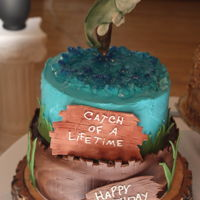 "Catch Of A Lifetime A 12"" 2 layer chocolate groom's cake with hazelnut filling. Covered in buttercream then fondant. Fish of gum paste using a mold..."